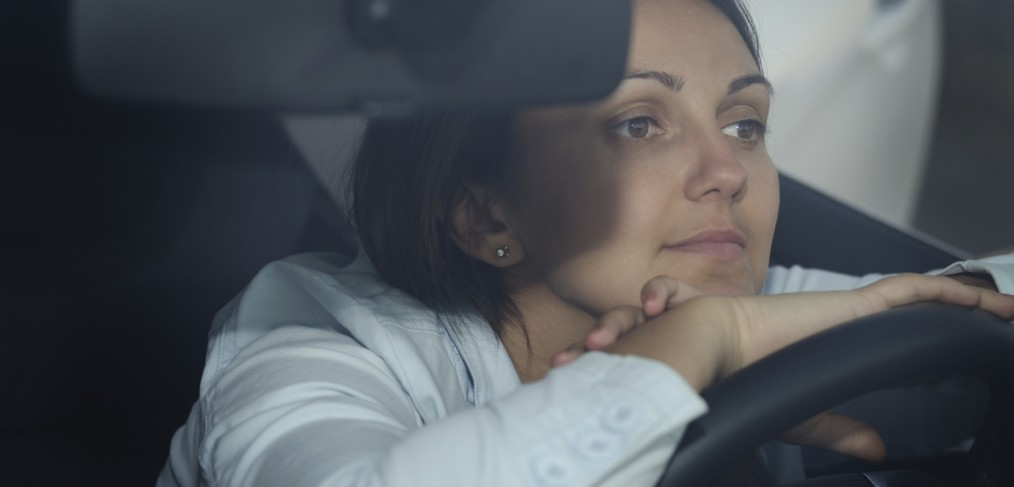 Participate - View through the windscreen of a woman sitting waiting in her car with hands and chin resting on the steering wheel