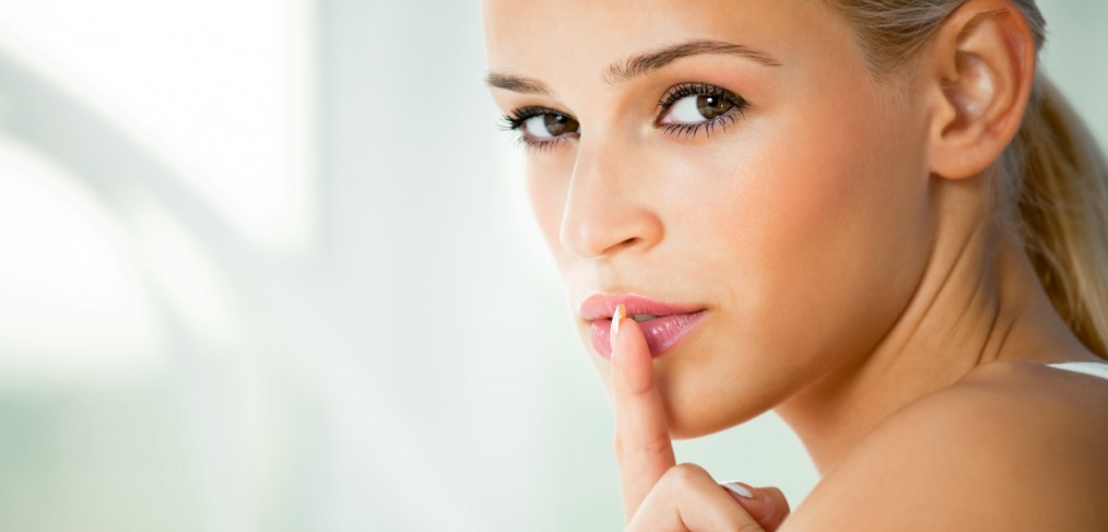 Portrait of young woman with finger on lips.
