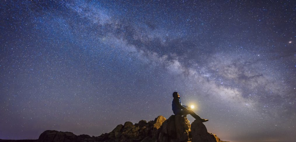 Dreams. Man sitting under The Milky Way Galaxy