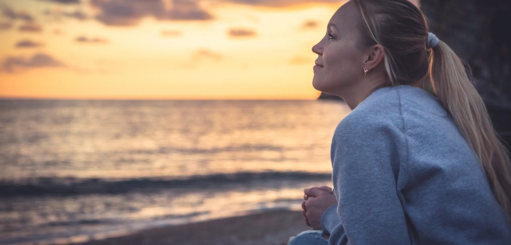 Thoughtful smiling woman looking with hope into horizon during sunset at beach