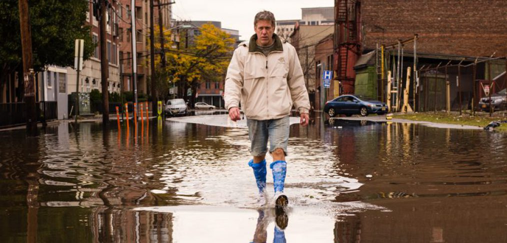 Crisis. Man walking on the flooded street after Hurricane Sandy landfall