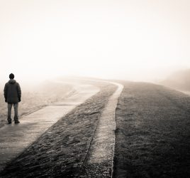 Uncertainty. A lonely man loosing the way on a foggy day.