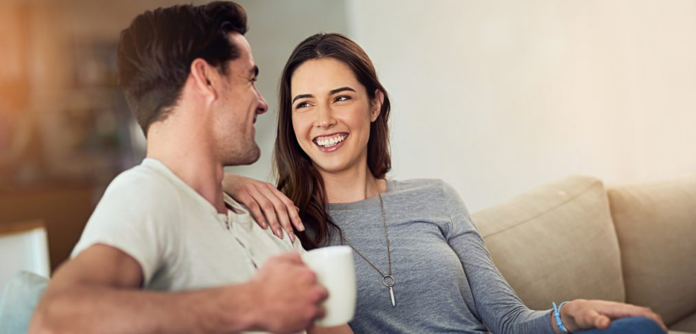 Present. Couple being present with each other while having coffee on a couch.
